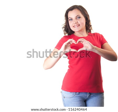 Attractive smiling girl in a red shirt  and blue jeans makes the sign of the heart with her fingers. Isolated on white background - stock photo