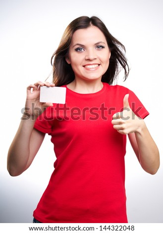 Attractive smiling girl in a red shirt holding a poster in her right hand and left hand showing thumbs up,on white background. - stock photo