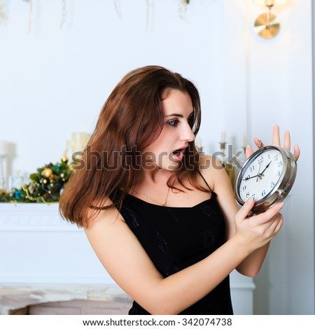 Attractive smiling girl stares at the clock with her mouth open, square frame. - stock photo