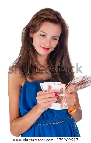 Attractive smiling girl with freckles cools herself with a fan of money