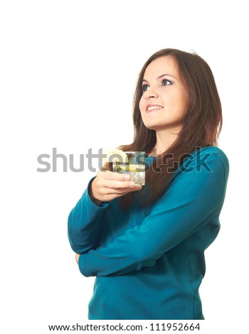 Attractive smiling girl with long dark hair in a blue blouse and jeans holding a glass of drink and looks right. Isolated on white background