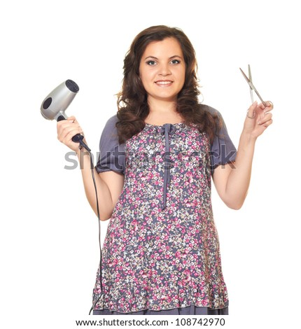 Attractive smiling girl with wavy long dark hair in a dress holding in his right hand hair dryer and in the left hand holding scissors isolated on white background