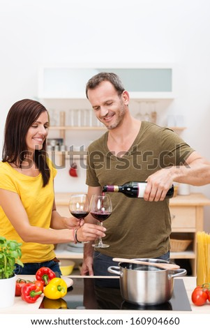 Attractive smiling man pouring his wife a glass of red wine as they stand together in the kitchen preparing a meal of spaghetti with fresh ingredients - stock photo