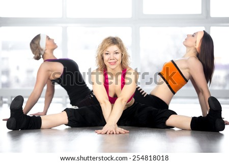 Attractive smiling mature mid age dancer female having choreography workout in group in fitness class, doing splits - stock photo