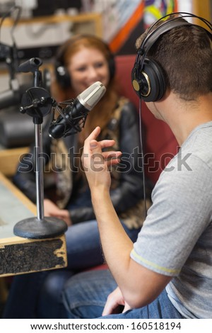 Attractive smiling radio host interviewing a guest in studio at college - stock photo