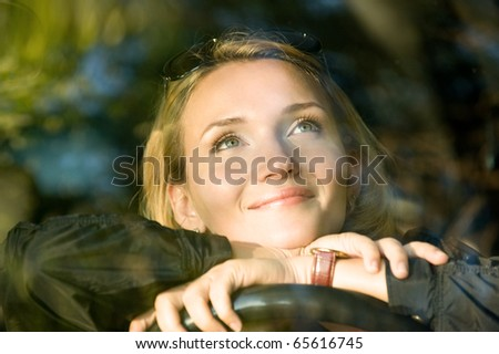 Attractive smiling woman dreams  in the new car and looking up - outdoors - stock photo