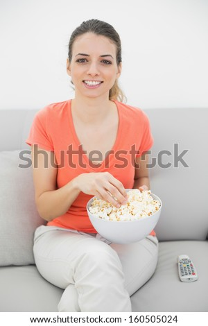 Attractive smiling woman eating popcorn while watching television ans sitting on couch - stock photo