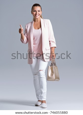 Attractive smiling woman holds the golden handbag. Young adult girl with thumb up sign. Cheerful lady in casual posing at studio.