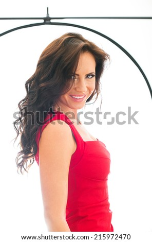 Attractive smiling woman shooting in photo studio. - stock photo