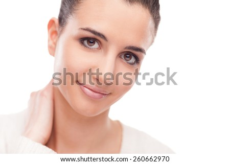 Attractive smiling woman touching her neck and posing on white background - stock photo