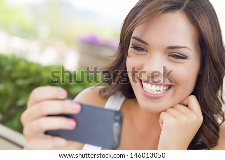 Attractive Smiling Young Adult Female Texting on Cell Phone Outdoors on a Bench. - stock photo