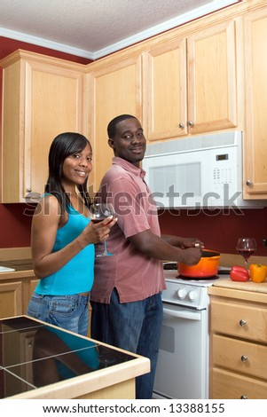Attractive smiling young African American couple cooking dinner together and drinking red wine.  Vertically framed shot with the man and woman looking towards the camera.
