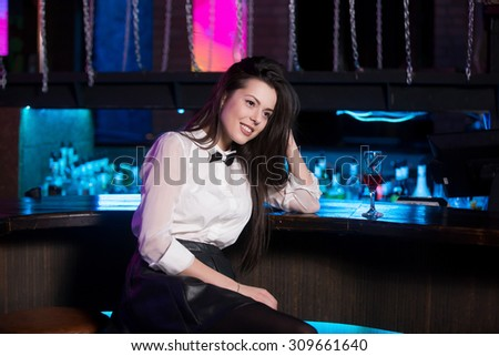 Attractive smiling young brunette woman wearing white shirt and black bow tie sitting at bar counter, relaxing with ordered glass of pink cocktail - stock photo