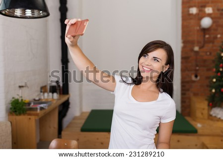 Attractive Smiling Young Female in White Shirt Taking Self Picture Inside the House. - stock photo