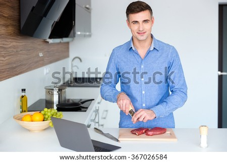 Attractive smiling young man in blue shit cooking meat on the kitchen at home - stock photo