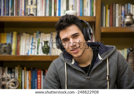 Attractive smiling young man listening to music on a set of stereo headphones in his study in front of a bookcase filled with books - stock photo