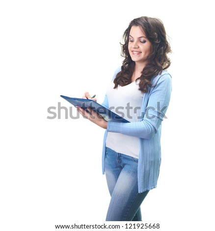Attractive smiling young woman in a blue shirt holding folder and writing something. Isolated on white background