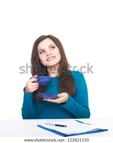Attractive smiling young woman in a blue shirt sitting at the table and drink from a blue cup. Documents are on the table. Isolated on white background