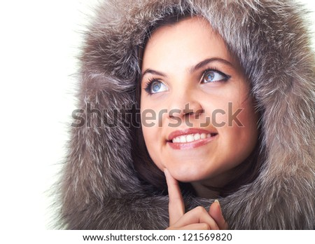 Attractive smiling young woman in a fur hood holding her finger on her chin and looks into the upper-right corner. Isolated on white background