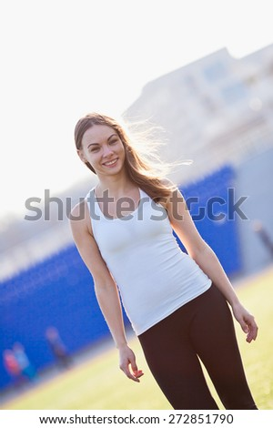 Attractive smiling young woman looking on camera after training on stadium. Angle view. Retro coloring - stock photo
