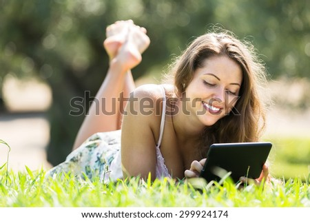 Attractive smiling young woman lying on grass in meadow and using tablet
