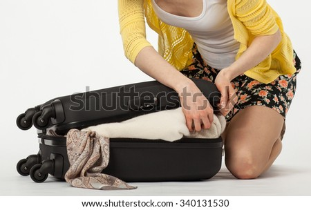 Attractive smiling young woman packing her suitcase - stock photo