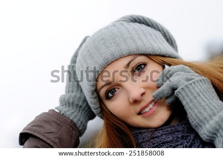 attractive smiling young woman wearing winter clothes using her smart phone