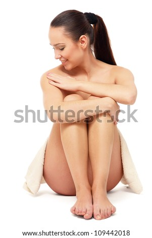 Attractive spa woman sitting on floor isolated on white background