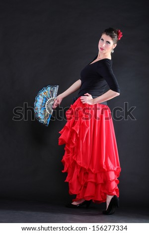 Attractive spanish dancer over black background young woman dancing flamenco - stock photo