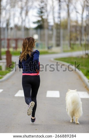 attractive sport girl running with dog in park - stock photo