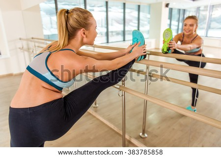 Attractive sport girl smiling and looking in the mirror while stretching the body in fitness class - stock photo