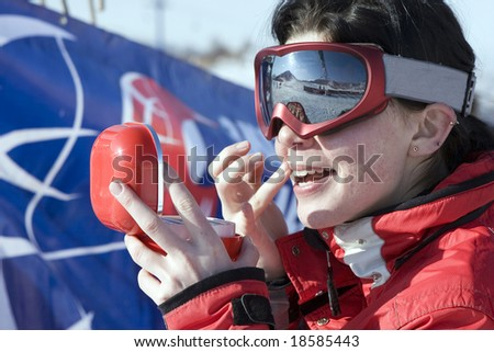 Attractive sport girl snowboarder applying face pack outdoors in winter mountain