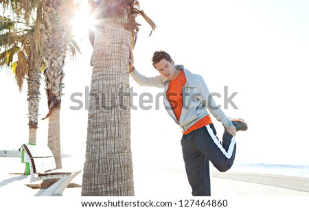 Attractive sports man stretching his leg while leaning on palm tree trunk by the sea with the sun shining through, getting ready for exercise. - stock photo