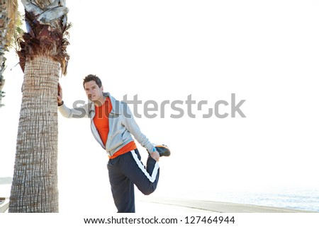 Attractive sports man stretching his legs while leaning on palm tree trunk by the sea in an open sky space. - stock photo
