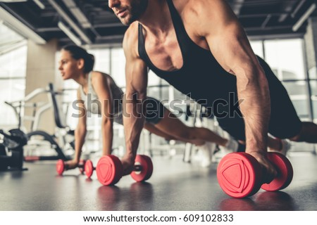 attractive sports people working out dumbbellsの写真素材