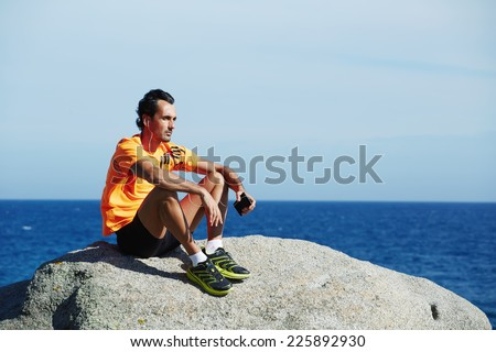 Attractive sportsman in bright sportswear listen music enjoying sunny summer day on the beach, fit man listening to music on his mobile smart phone while resting after run outdoors, enjoying music - stock photo