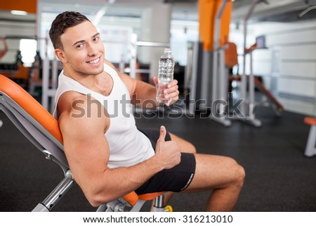 Attractive sportsman is sitting on bench in gym and relaxing. He is holding a bottle of water and drinking it with pleasure. The man is looking at the camera and smiling. He is giving thumb up - stock photo