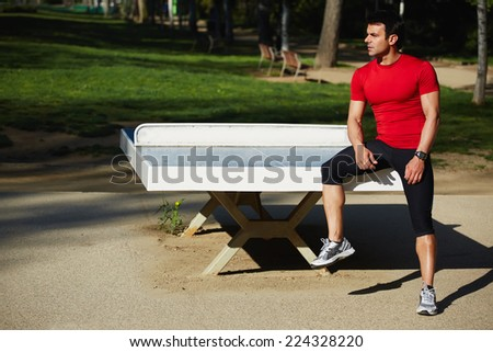 Attractive sportsman sitting on the tennis table resting after intensive evening run, beautiful fit man with perfect muscular body taking break in beautiful park at sunny summer evening, sport concept - stock photo