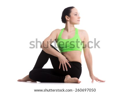 Attractive sporty girl doing yoga training, Half lord of the fishes pose, Ardha Matsyendrasana, one of the basic asana in Hatha Yoga - stock photo