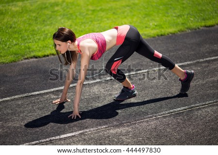 Attractive sporty girl ready to run sprint. Female athlete in powerful starting line pose. - stock photo