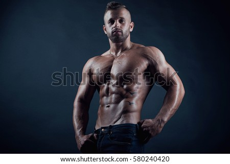 Attractive sporty handsome sexy muscular young adult male fitness model with abs tattoo portrait