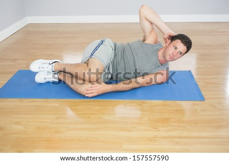 Attractive sporty man doing abdominal crunch in bright room - stock photo