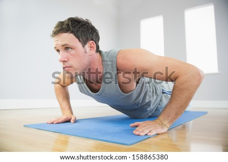 Attractive sporty man doing push ups on blue mat in bright room - stock photo