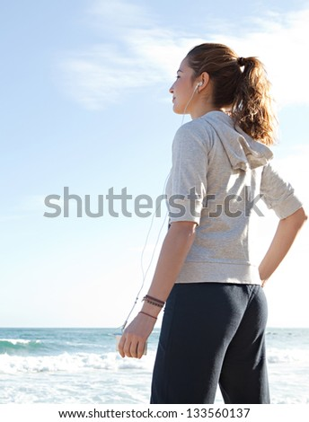 Attractive sporty young woman standing on the beach taking a break from exercising and listening to music with her mp4 player and head phones against a blue sky.