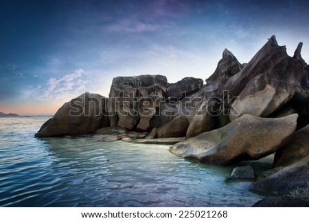 Attractive Spot of Huge Rocks at Seychelles at the Side of Beautiful Blue Water Sea. Captured on Gradient Blue Sky Above. - stock photo