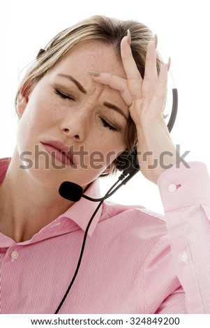 Attractive Stressed Young Business Woman Using a Telephone Headset Making Sales Calls or Marketing Against a Plain White Background - stock photo