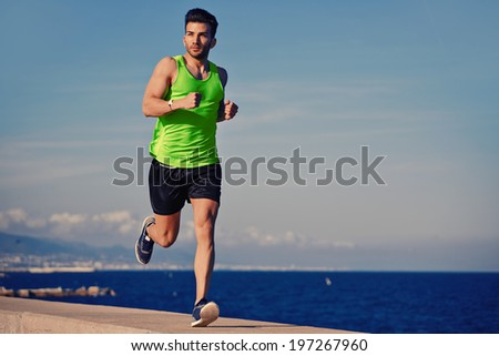 Attractive strong athlete jogging along the sea and looking away