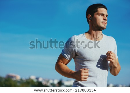 Attractive strong athlete running along the sea  - stock photo