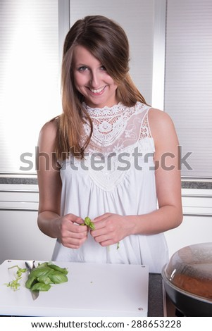 attractive student cooking bolognese sauce in kitchen - stock photo