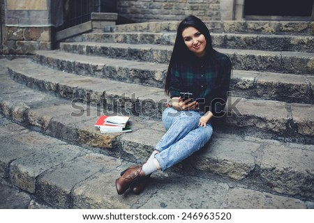 Attractive student girl resting outdoors during her class break in college, laughing female tourist girl holding mobile phone in the hand looking to the camera - stock photo